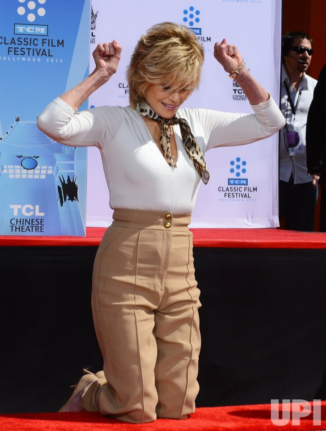 Jane Fonda places hands and footprints in wet cement at TCL Chinese Theatre in Los Angeles