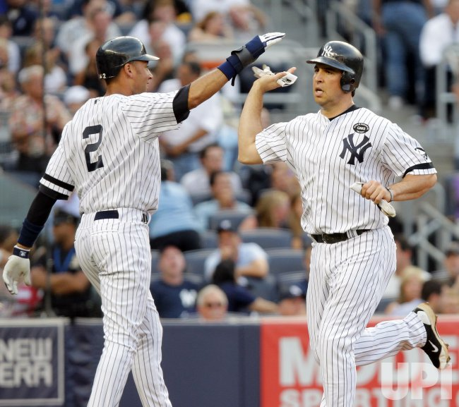 New York Yankees Derek Jeter slaps hands with Mark Teixeira at Yankee Stadium in New York