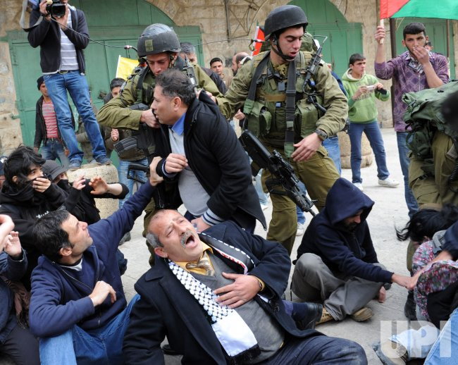 Israeli soldiers arrest a Palestinian during a protest against the closure of Shuhada Street in Hebron, West Bank