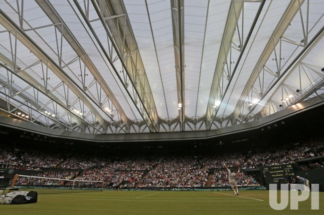 Andy Murray serves under the roof at 2013 Wimbledon Championships