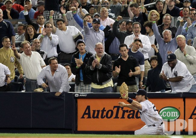 Fans react after New York Yankees Mark Teixeira makes a catch at Yankee Stadium in New York