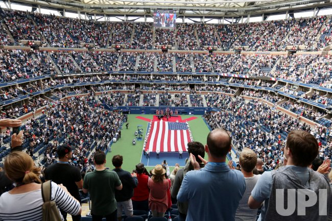 A giant American Flag is displayed the opening ceremony at the men's championship match at the US Open