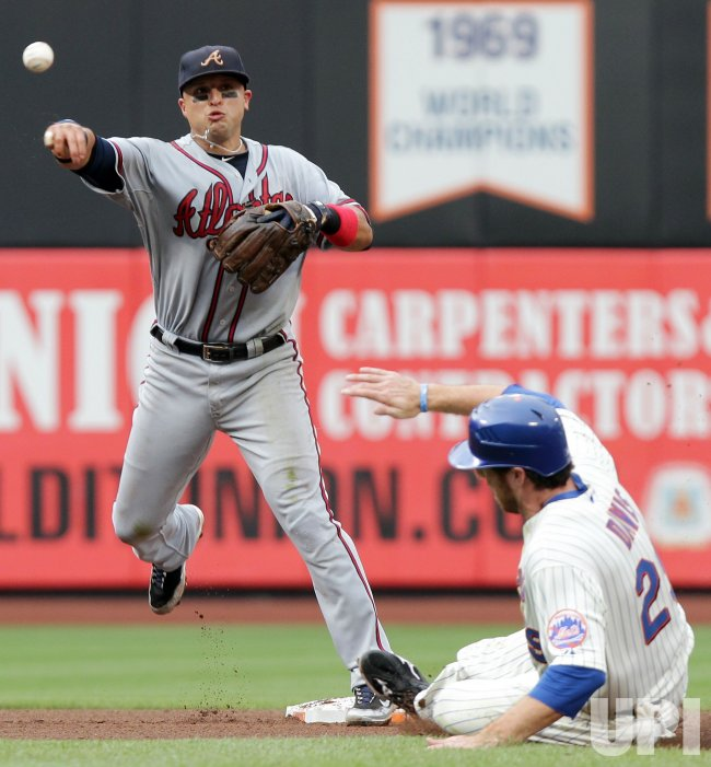 Atlanta Braves Martin Prado throws to first base for a double play while New York Mets Ike Davis slides into second base at Citi Field in New York
