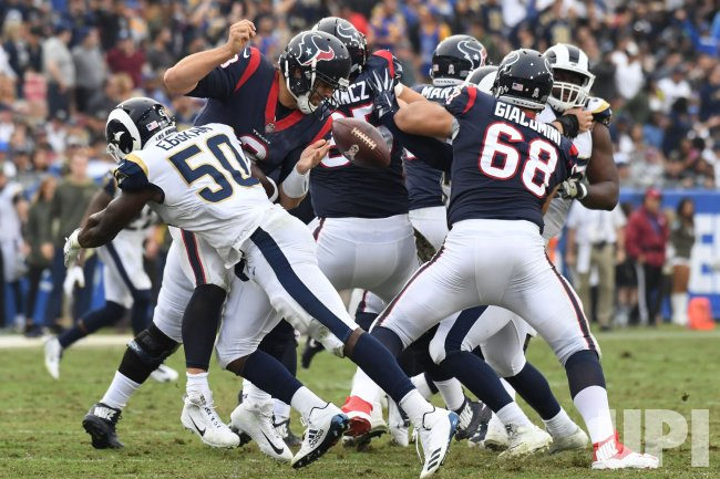 Texans' quarterback Tom Savage fumbles after being tackled by Rams linebacker Samson Ebukam (50) in Los Angeles, California