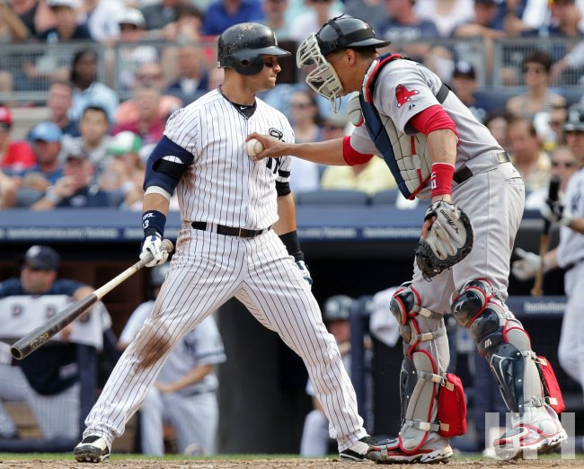 New York Yankees Nick Swisher is tagged out by Boston Red Sox Victor Martinez at Yankee Stadium in New York