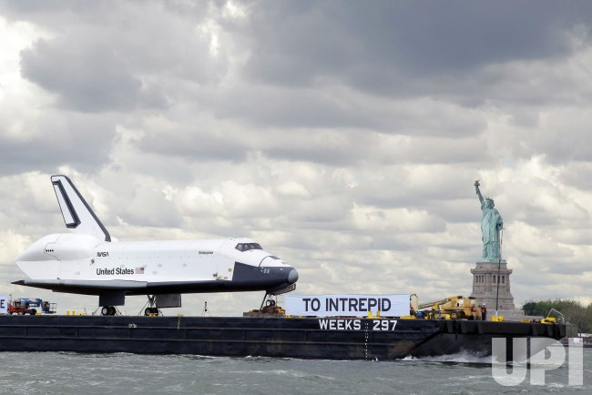 Space Shuttle Enterprise passes Statue of Liberty and the