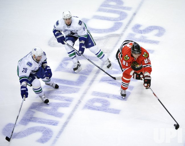 Blackhawks Hossa skates with puck as Canucks Parent and Burrows defend in Chicago