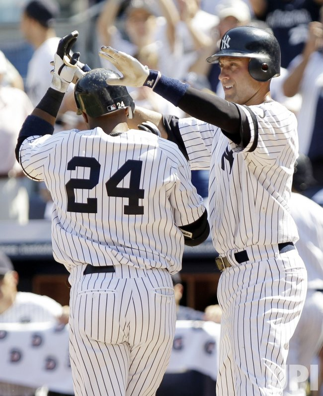 New York Yankees Robinson Cano slaps hands with Derek Jeter at Yankee Stadium in New York