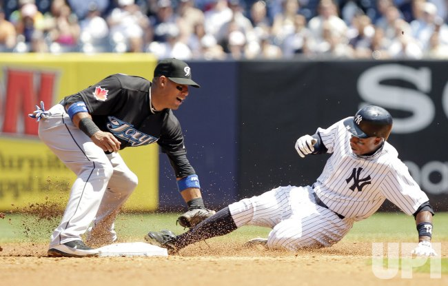New York Yankees Curtis Granderson slides under the tag of Toronto Blue Jays Aaron Hill at Yankee Stadium in New York