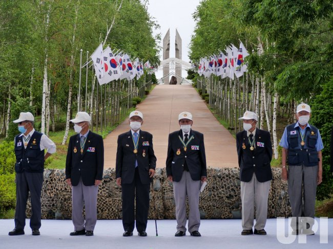 A Group of Korean War Veterans Stand on Stage