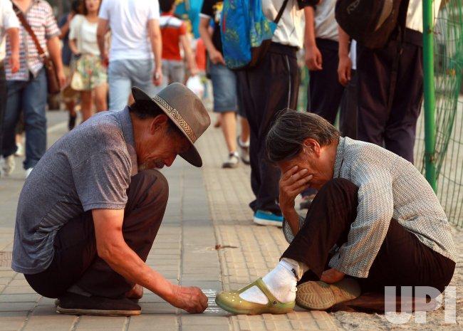 An elderly Chinese couple write a plea for financial help in Beijing