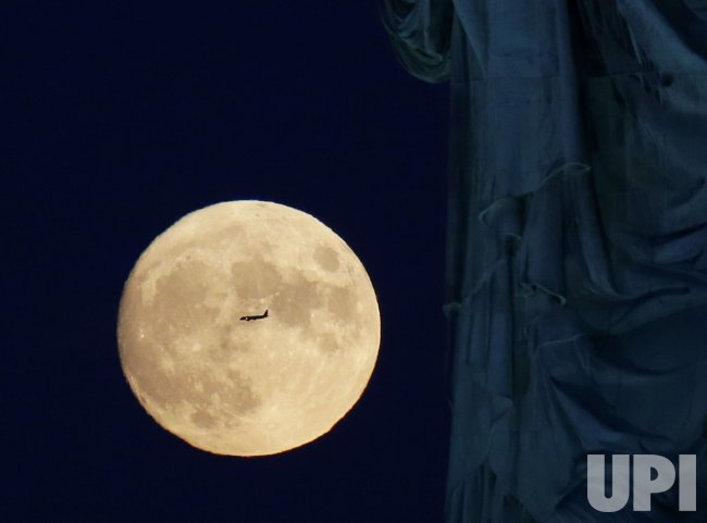 Full Moon Rises Behind the Statue Of Liberty