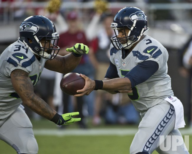 Seahawks QB Russell Wilson hands off to Thomas Rawls