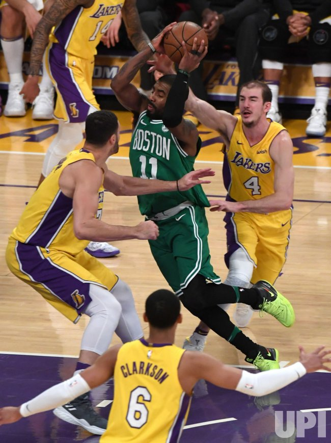 Celtics Kyrie Irving drives between Lakers Larry Nance Jr (L) and Alex Caruso (R)
