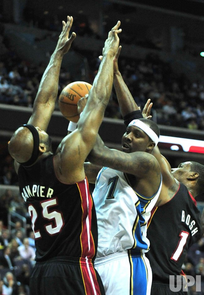 Wizards' Andray Blatche is blocked by Miami Heat's Erik Dampier and Chris Bosh in Washington
