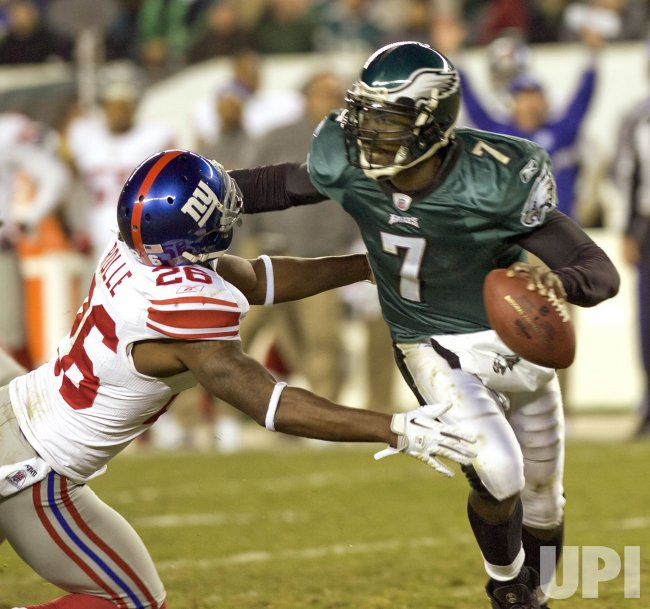 Philadelphia Eagles quarterback Michael Vick pushes New York's Antrel Rollie away in the 4th quarter.