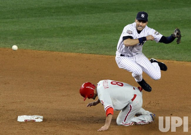 New York Yankees Derek Jeter leaps over Philadelphia Phillies Shane Victorino and throws to first base for a double play in the eighth inning in game 2 of the World Series at Yankee Stadium in New York