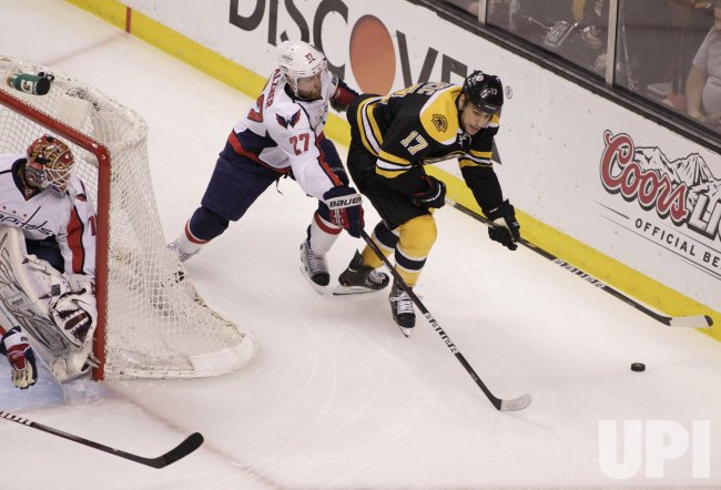 Bruins Lucic skates around Alzner and Capitals at TD Garden in Boston, MA.