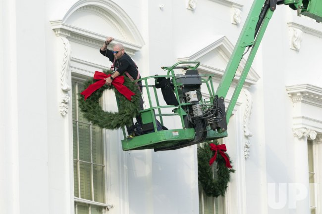 A worker installs holiday wreaths on the White House