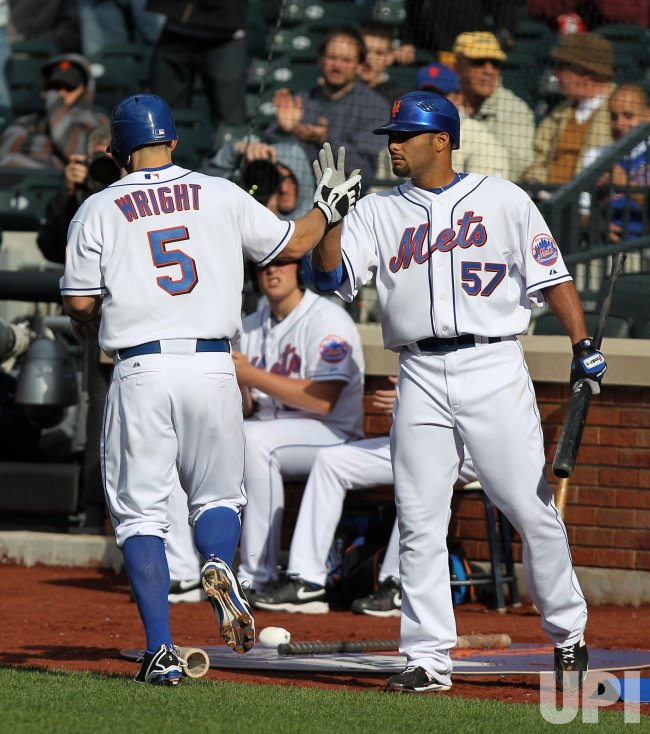 New York Mets starting pitcher Johan Santana slaps hands with David Wright at Citi Field in New York
