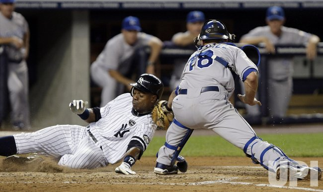New York Yankees Curtis Granderson slides safely into home past Kansas City Royals Jason Kendall at Yankee Stadium in New York