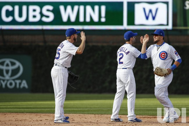 Cubs Kyle Schwarber celebrates with Mike Freeman and Tommy La Stella after defeating Reds in Chicago