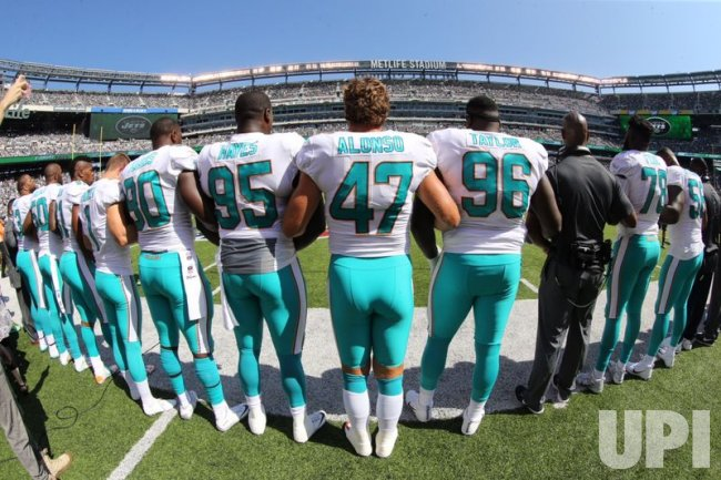 Miami Dolphins lock arms before playing Jets