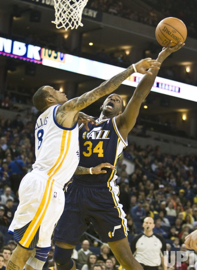 Utah Jazz C.J. Miles puts up a shot against Golden State Warriors Monta Ellis in Oakland, California
