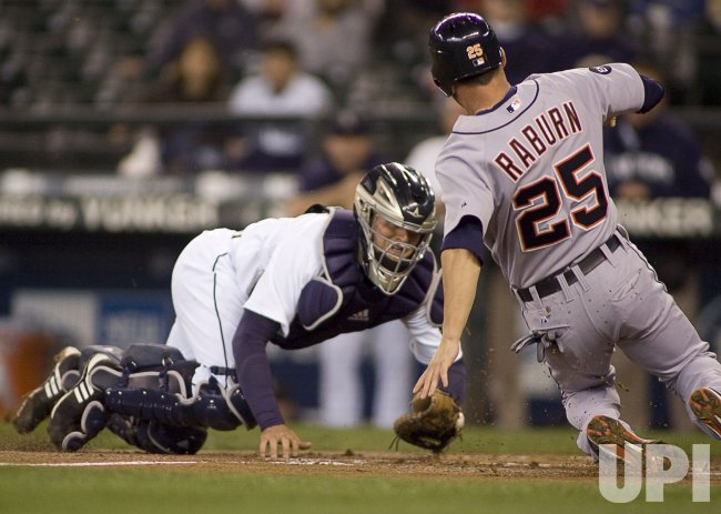 Seattle Mariners' catcher Josh Bard (L)guards the plate as Detroit Tigers' Ryan Raburn tires to score from third in the first inning.