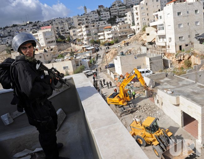An Israeli police guard the site of a building being demolished in east Jerusalem