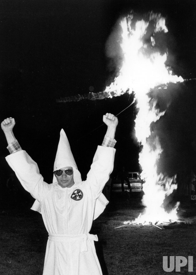 A member of the Ku Klux Klan raises his fists during a cross burning.
