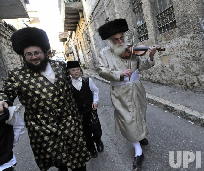 An Ultra-Orthodox Jew prays the violin on the street on Purim in Jerusalem