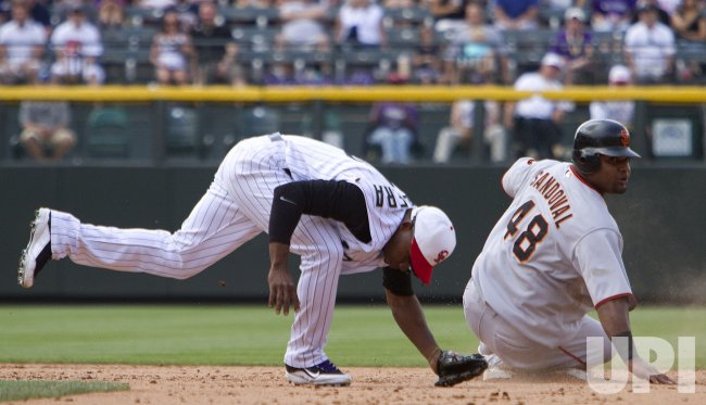Rockies Herrera Completes a Double Play over Giants Sandoval in Denver