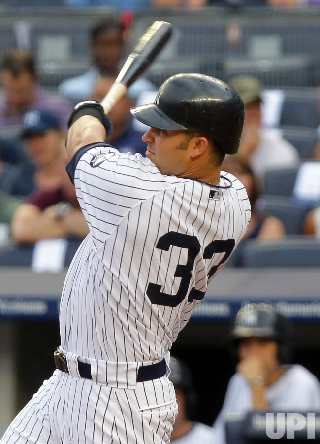 New York Yankees Nick Swisher hits a solo homer at Yankees Stadium in New York