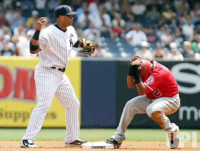 New York Yankees Robinson Cano holds his throw to first base while Los Angeles Angels Erick Aybar covers his head at Yankees Stadium in New York