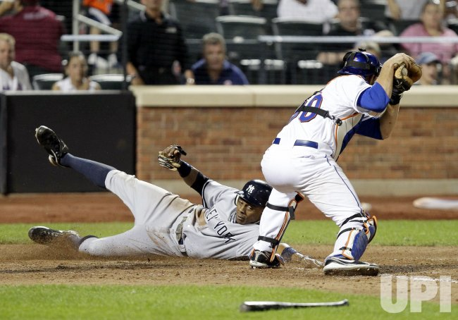 New York Yankees Curtis Granderson slides past New York Mets Josh Thole at Citi Field in New York