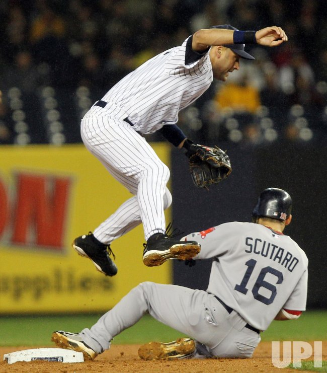 New York Yankees Derek Jeter leaps over Boston Red Sox Marco Scutaro while trying to complete a double play at Yankee Stadium in New York