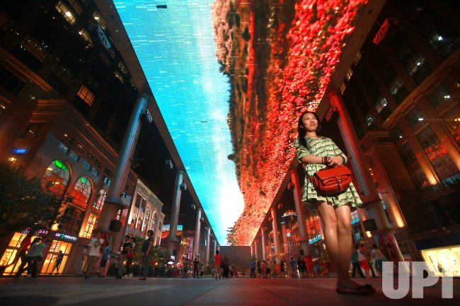 A Chinese woman poses for a photo below one of the world's largest LED screens in Beijing