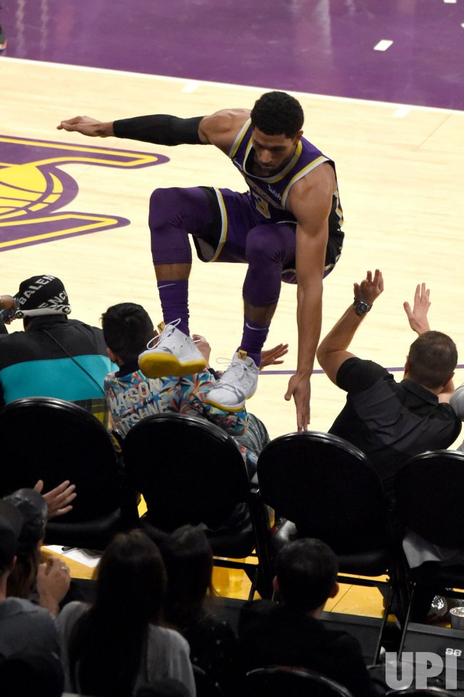 Lakers guard Josh Hart jumps over the front row of fans