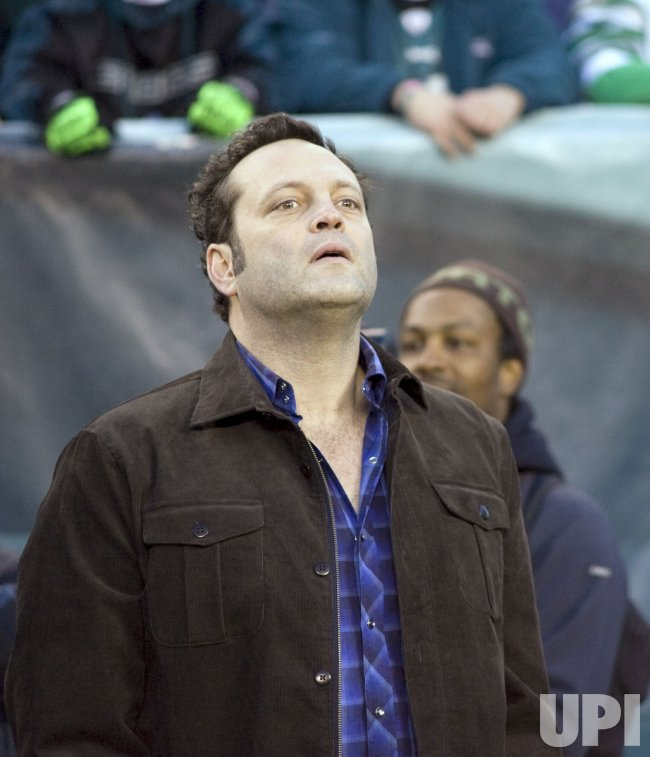 Actor Vince Vaughn takes in the football acton ont he sideliens
