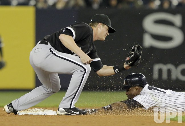 New York Yankees Curtis Granderson slides safely under the tag of Gordon Beckham at Yankee Stadium in New York