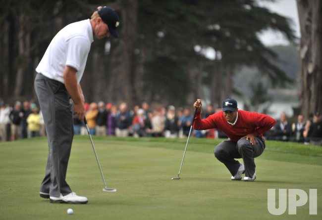Tiger Woods and Steve Stricker line up a putt during the first round of the 2009 Presidents Cup in San Francisco