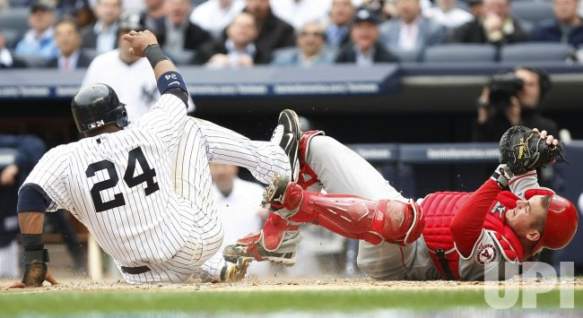 New York Yankees Robinson Cano slides into Los Angeles Angels of Anaheim catcher Jeff Mathis on opening day at Yankee Stadium in New York
