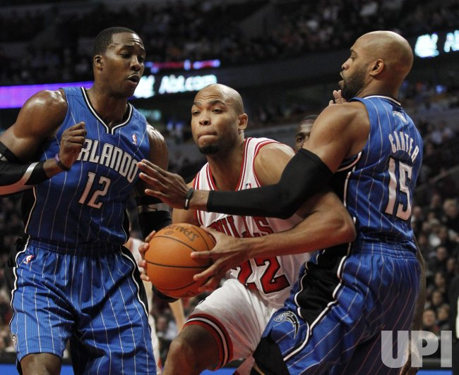 Bulls Gibson drives on Magics Howard, Carter in Chicago