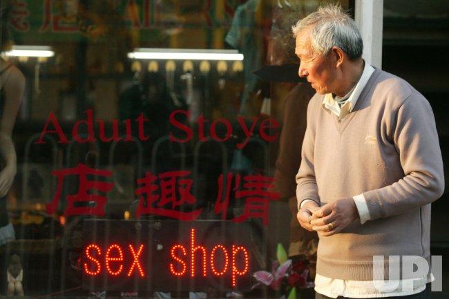Chinese man walks past sex shop in Beijing