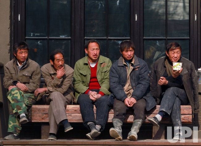 Chinese migrant workers sit in the sun Beijing