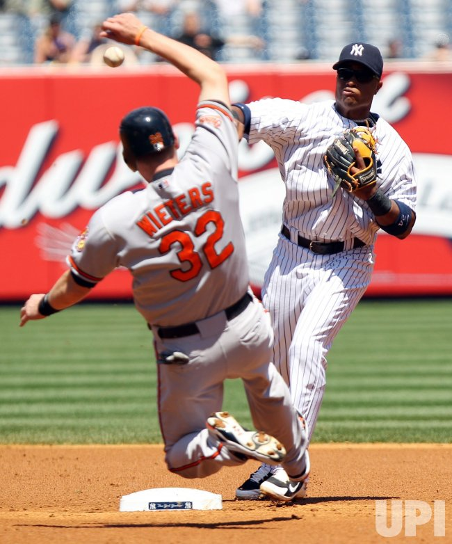 Baltimore Orioles Matt Wieters slides into second base and New York Yankees Robinson Cano throws to first base at Yankee Stadium in New York