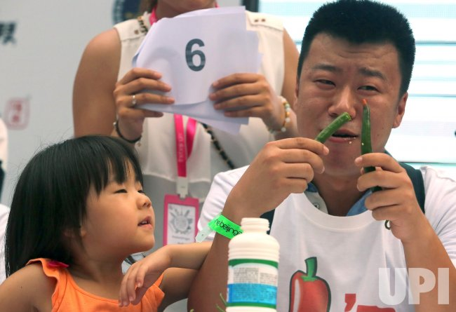 A Chinese Man Is Encouraged By His Daughter In A Chili Eating