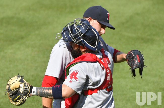 Red Sox relief pitcher Matt Barnes greeted by catcher Sandy Leon after 7-3 win over Orioles