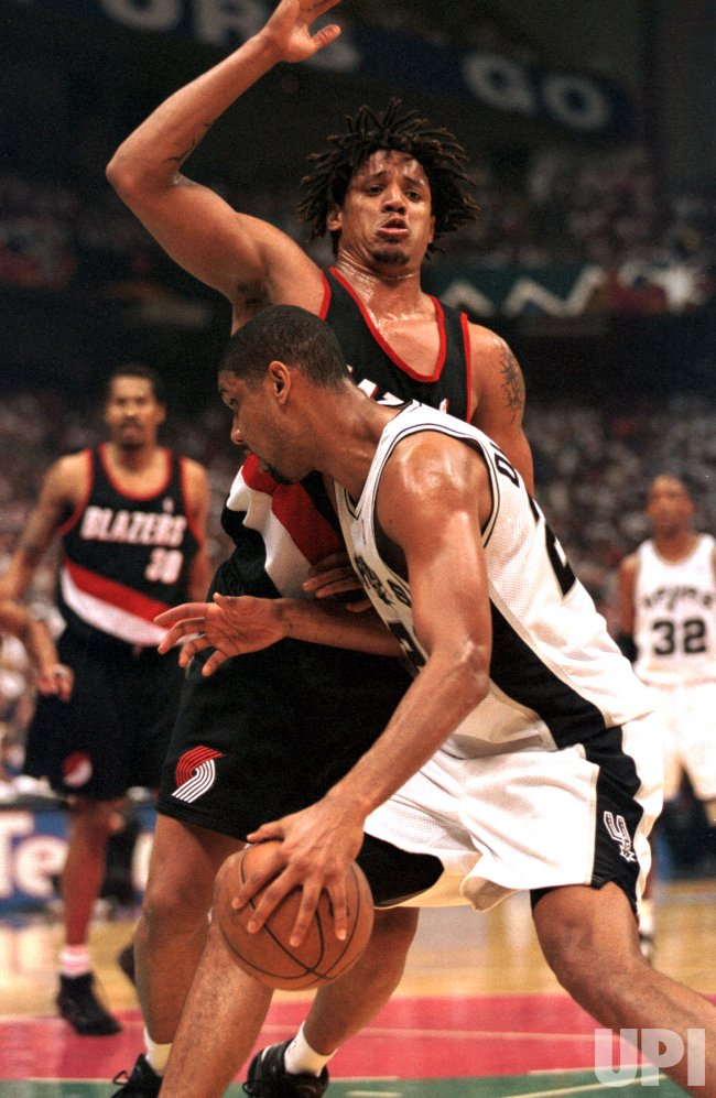 San Antonio Spur Tim Duncan (21) drives into Portland Trailblazer Brian Grant (44)